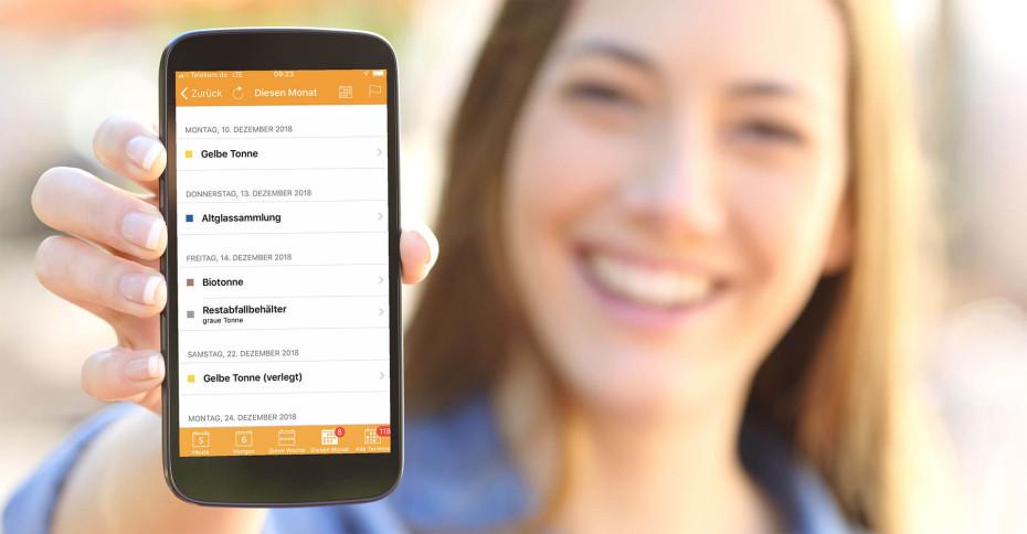 Lachende Frau hält Smartphone ins Bild auf dem Daten der Abfall-App zu sehen sind.