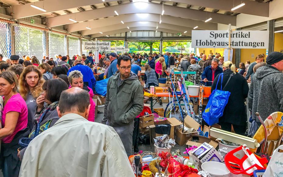 Menschen schauen sich in der Freilufthalle Iffezheim an den verschiedenen Warentischen um