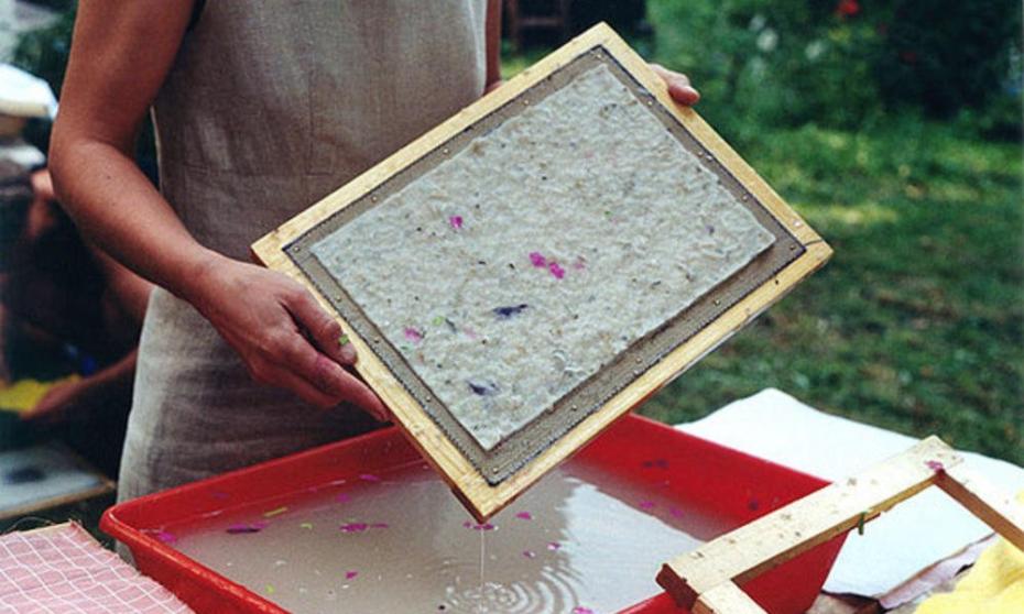 Frau hält selbstgeschöpftes Papier in den Händen