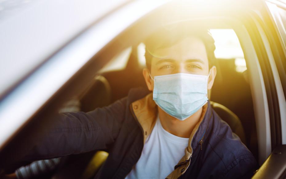Mann in Auto mit Mundschutz